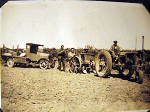 Walter Mark Oakley driving tractor with employees, using a pre 1924 truck and planting potatoes, 1935.